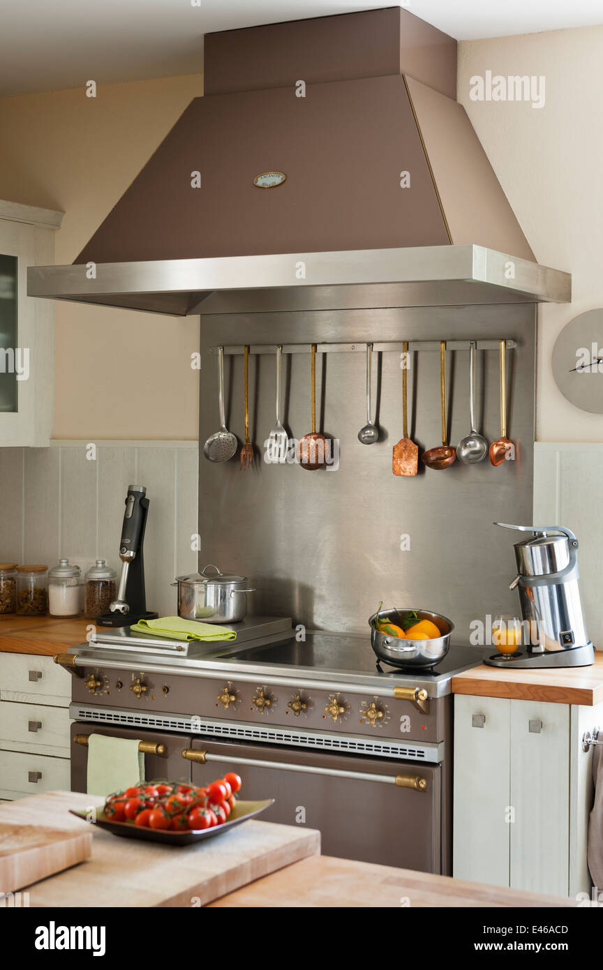 Copper and steel kitchen utensils hanging from rack part of a La Canche cooker - Stock Image