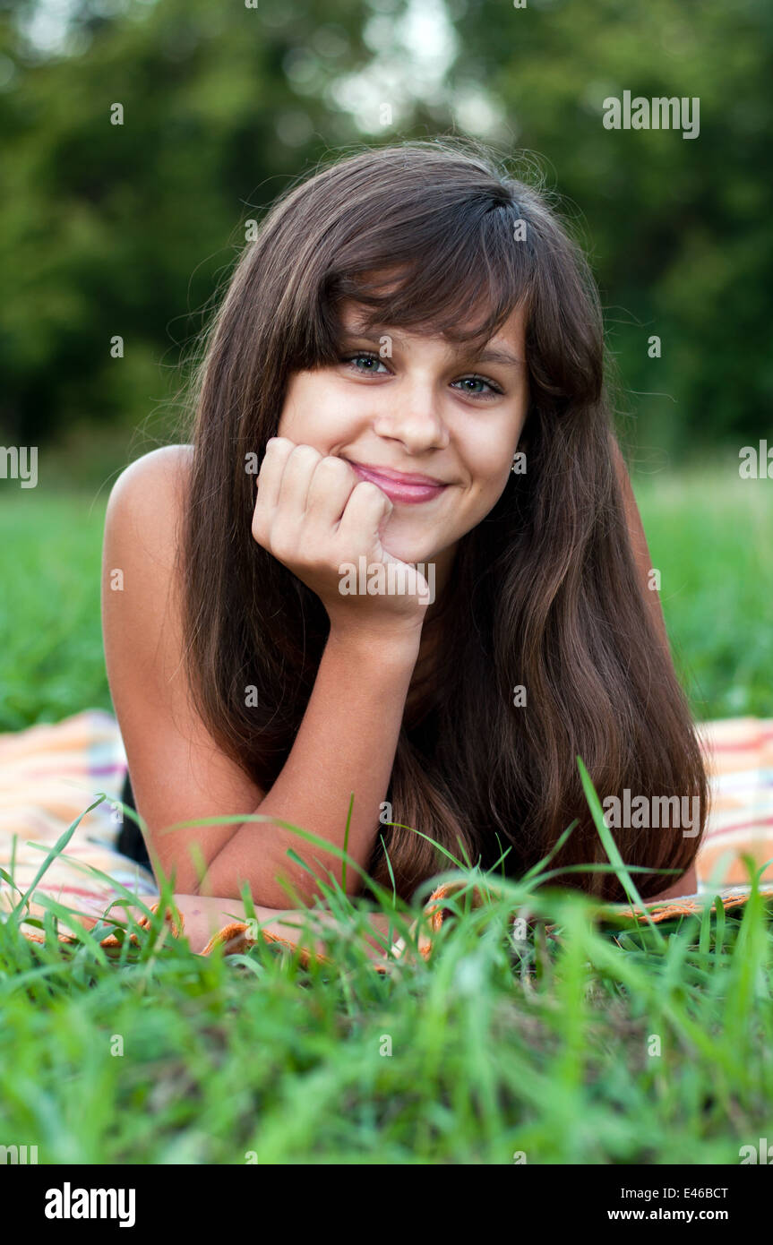 girl teen teenager transition age 13 14 15 years brunette hair long dark nature park open air beautiful portrait Stock Photo