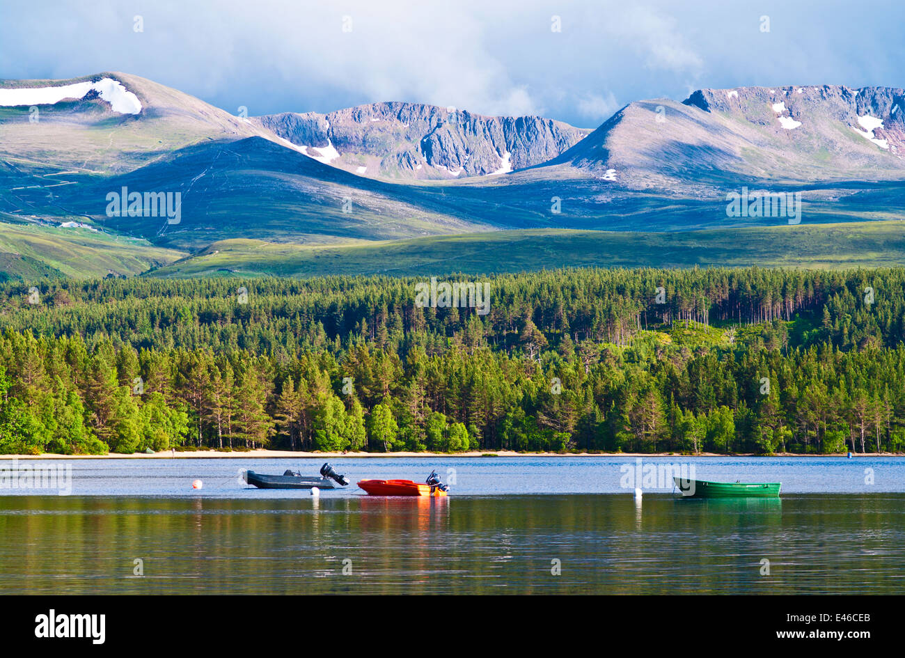 Coire an t-Sneachda rises above Glenmore Forest and boats moored on Loch Morlich, the Cairngorms near Aviemore, - Stock Image