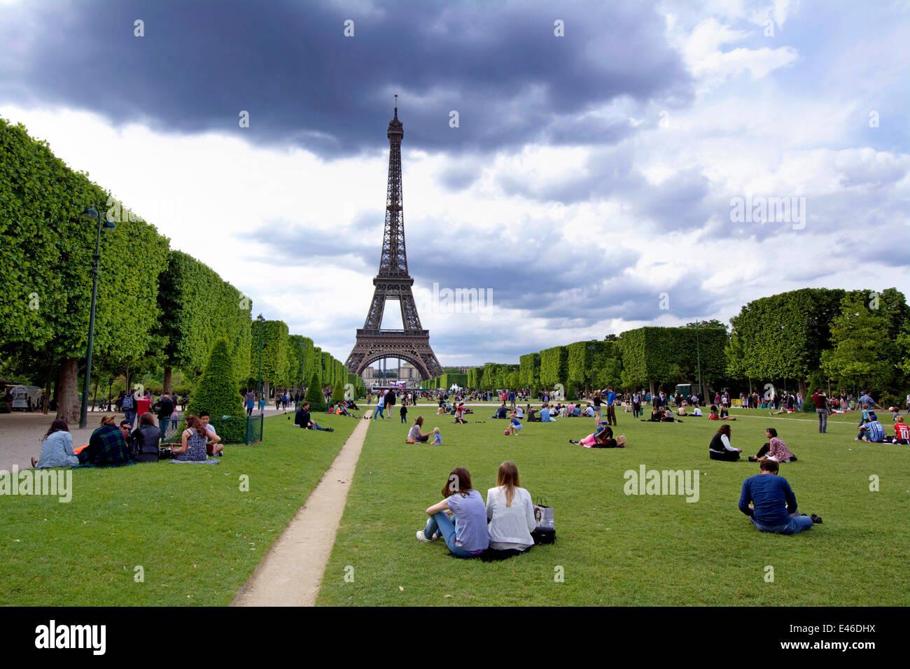 The Eiffel Tower and the Parc du Champ de Mars with tourists, Paris, France - Stock Image