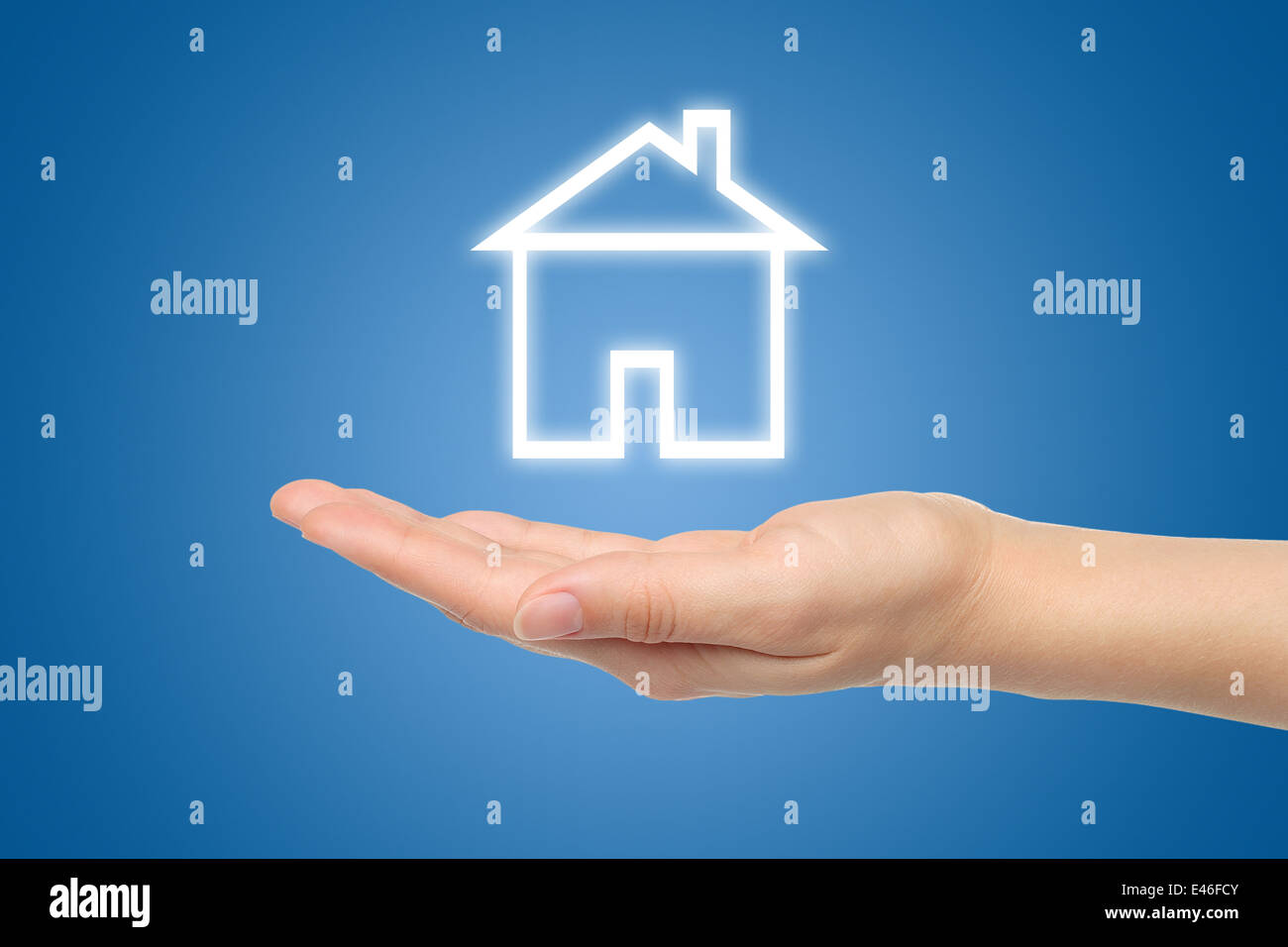 Virtual house with woman hand on blue background - Stock Image