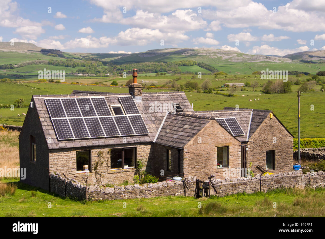 A remote house with solar panels in the Forest of Bowland, looking across to the Yorkshire Dales, UK. - Stock Image