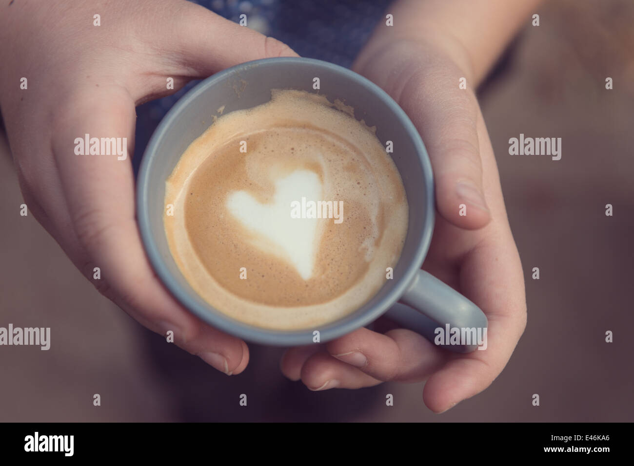 hands holding a grey cup with a love heart shape in the crema - Stock Image