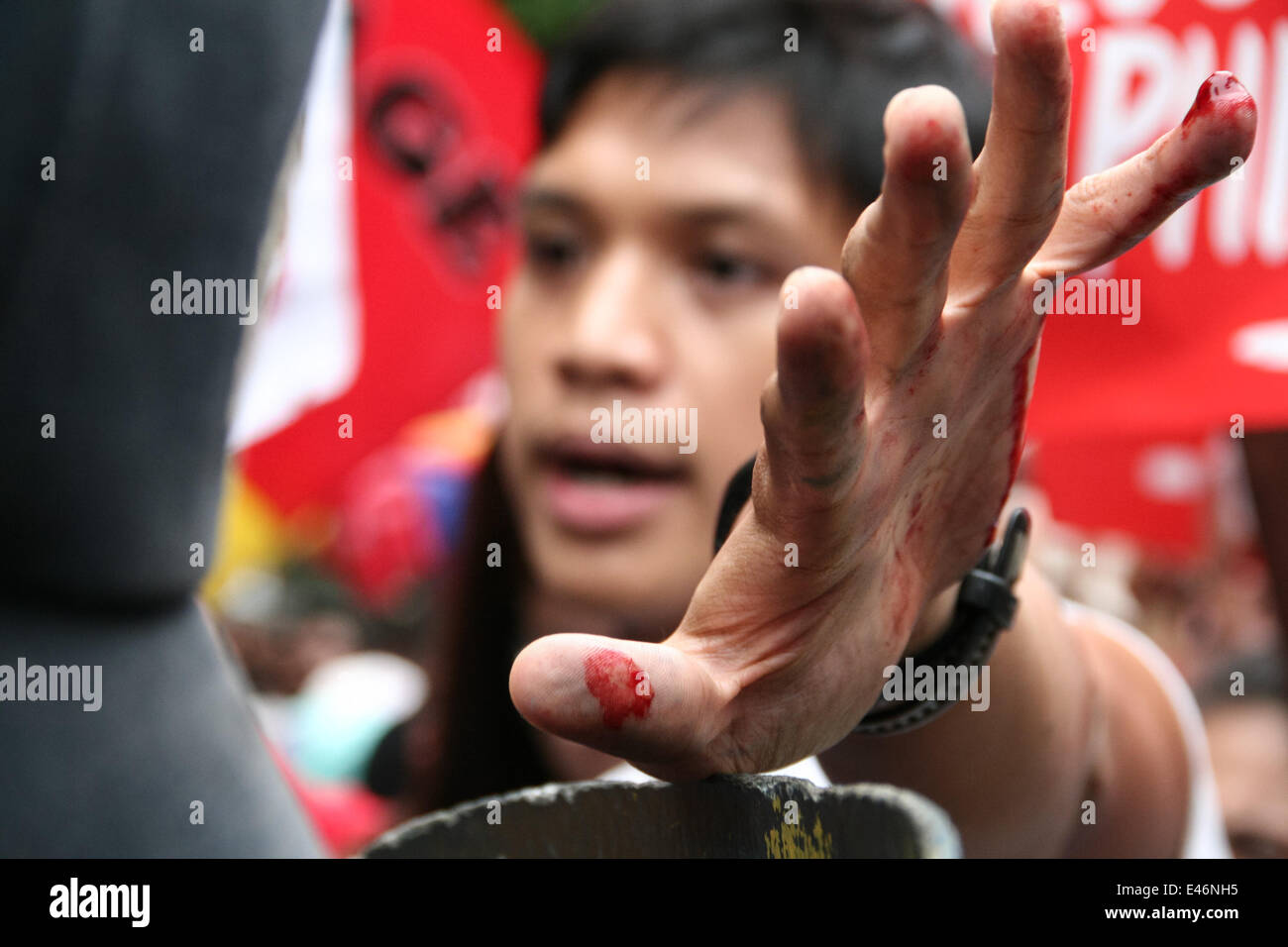 Manila, Philippines. 4th July, 2014. Vencer Crisostomo, Anakbayan chairperson, places his bloody hands on top of - Stock Image