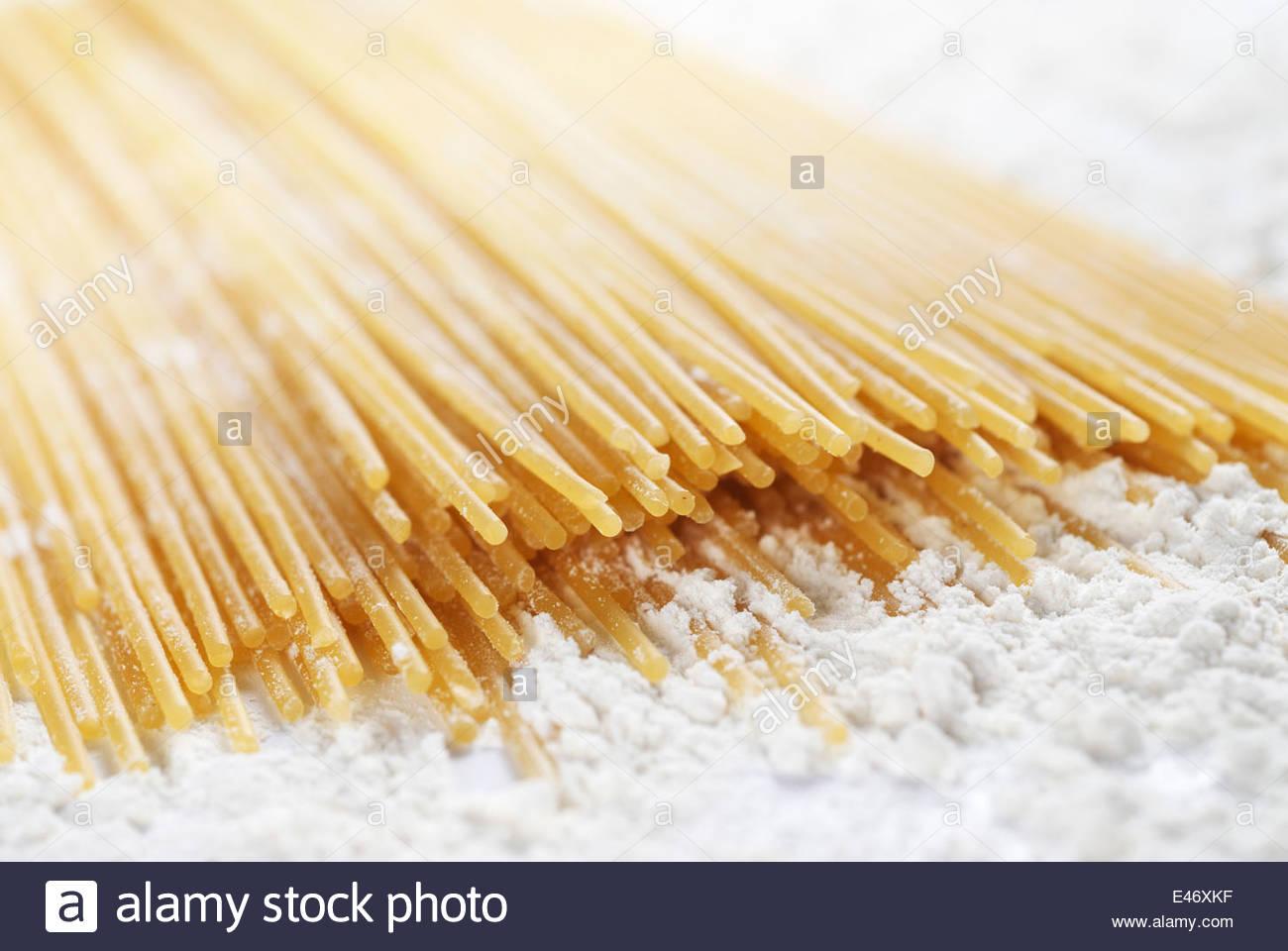 Closeup of raw spaghetti pasta with flour - Stock Image