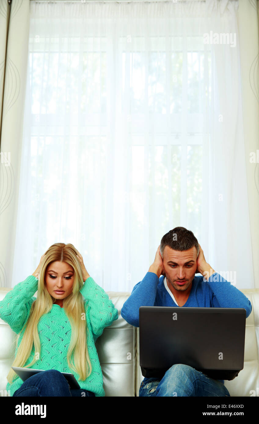 Scared couple sitting on the sofa with tablet computer and laptop - Stock Image