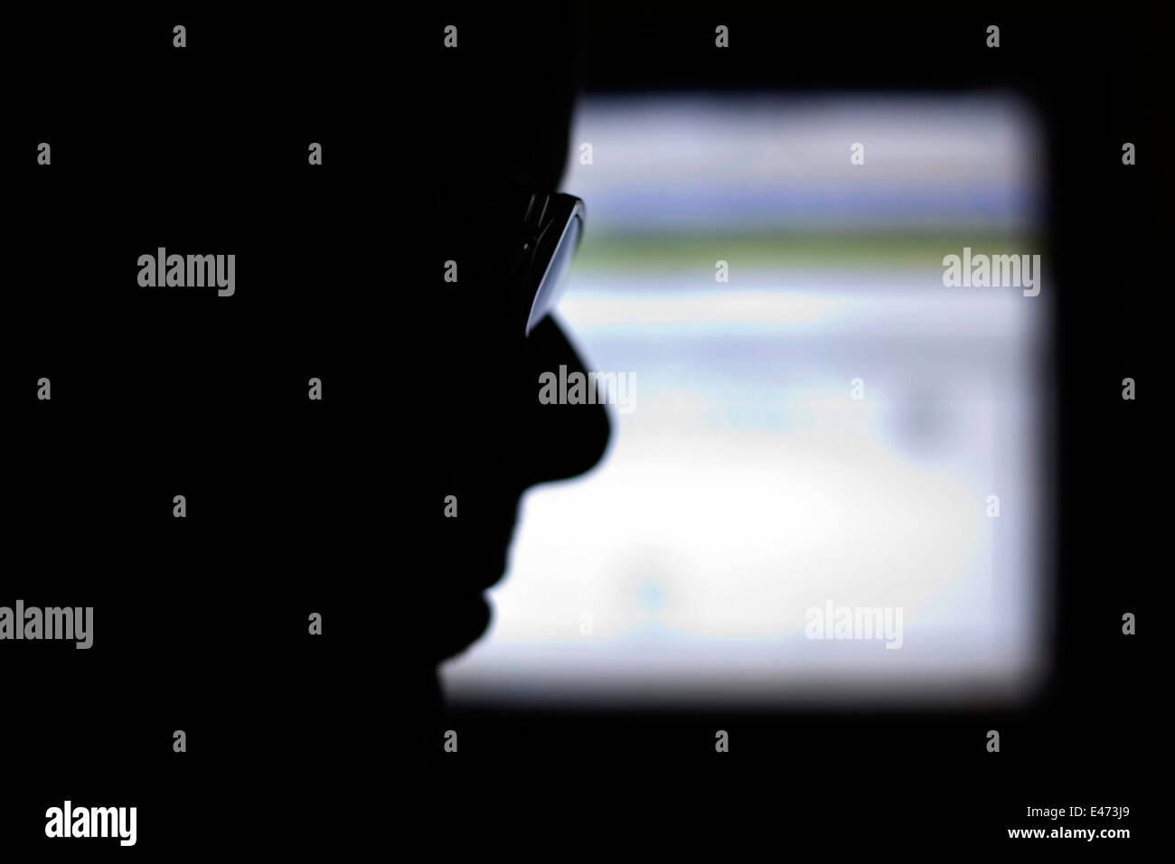 An irrecognizeable man silhouettte near a computer screen. - Stock Image