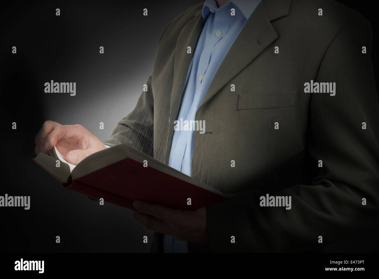 book of knowledge see the light, a man in a suit reading a book light from the pages. - Stock Image