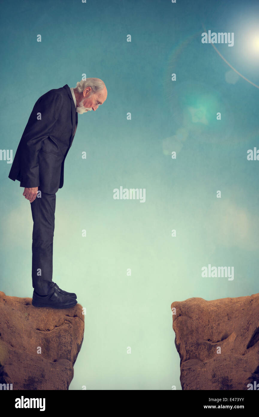 senior man looking down a mountain crevasse - depression or suicide concept - Stock Image