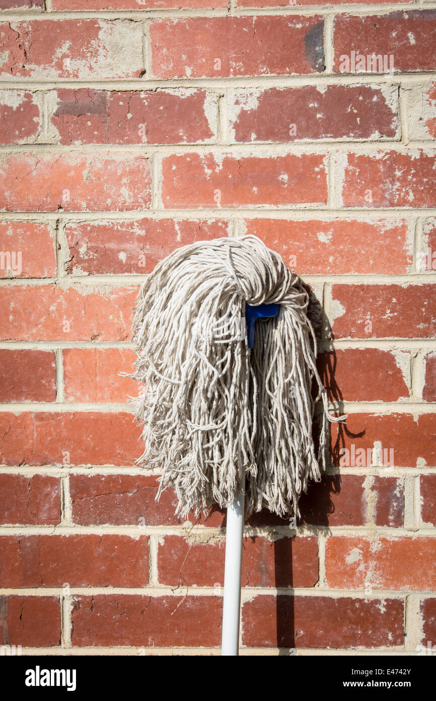 the new mop as still life on the brick wall - Stock Image