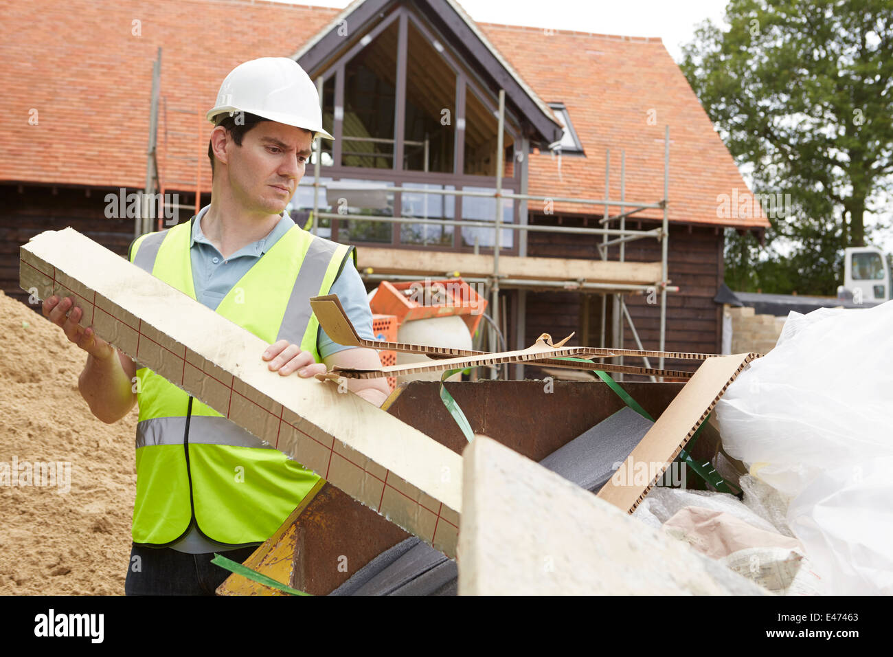 Builder Throwing Waste Into Skip On Construction Site - Stock Image
