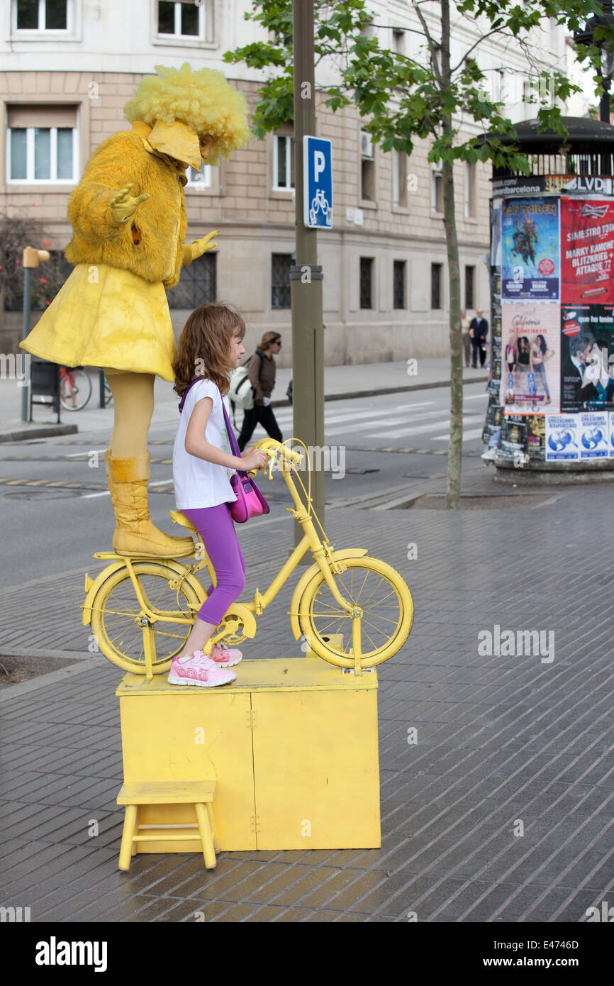Street mime artist acting as the Equilibrist, posing with little girl on La Rambla in Barcelona, Catalonia, Spain. - Stock Image