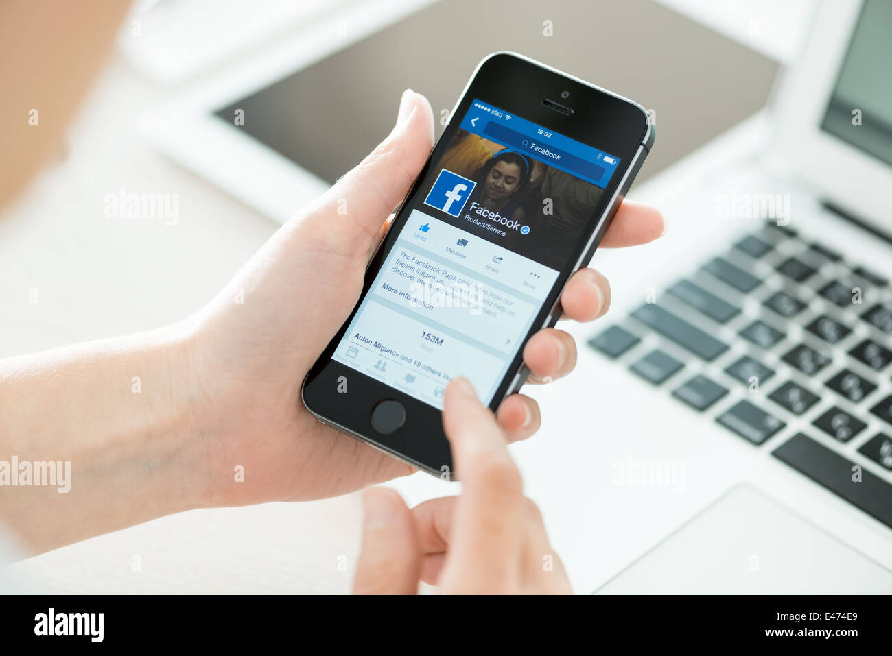 Person holding a brand new Apple iPhone 5S with Facebook profile on the screen - Stock Image