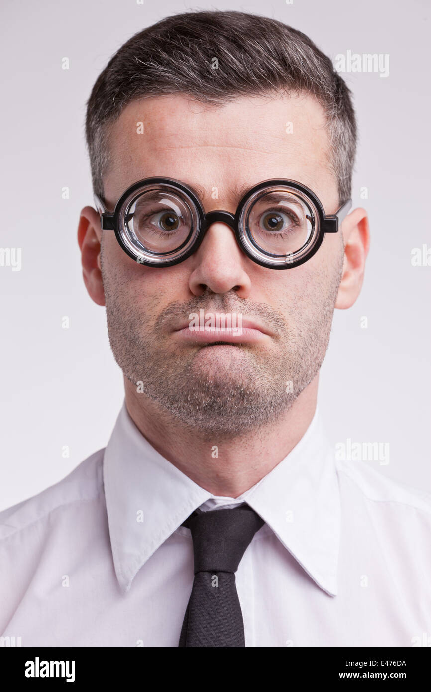 an upset and disappointed nerd clerk staring at camera very unhappy - Stock Image