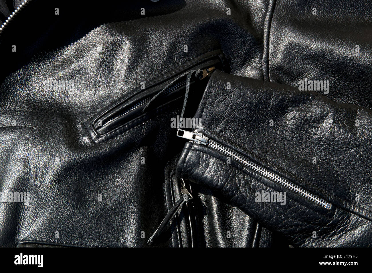 High contrast close up of black leather motorcycle jacket showing zippered pockets and portion of sleeve in sunshine. - Stock Image