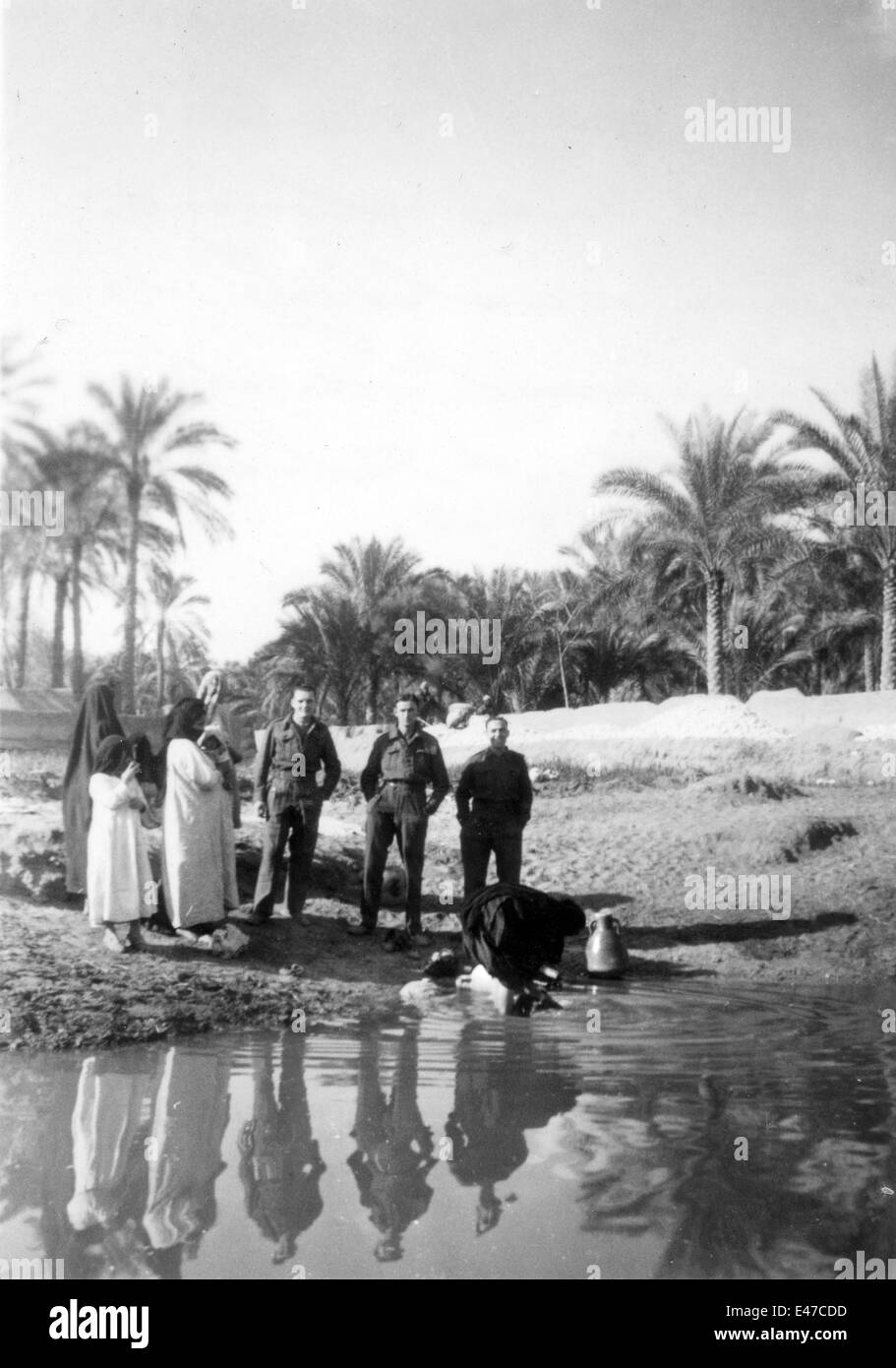British REME soldiers watch local women washing in the sweet water canal at Tel-el-Kebir Egypt 1943 during World - Stock Image