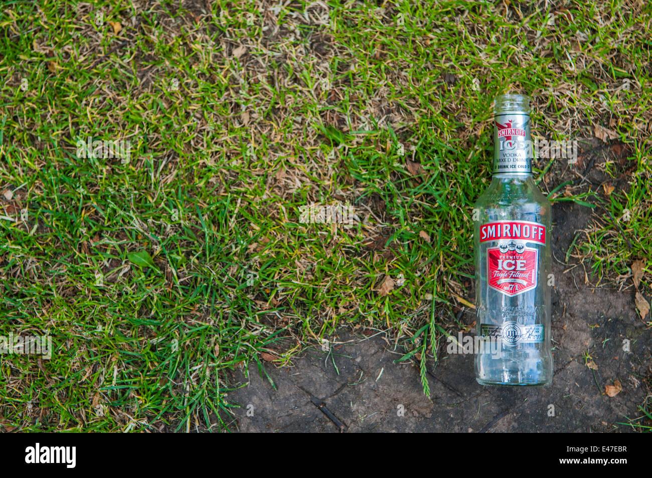 Smirnoff Ice bottle littering a grass area - Stock Image