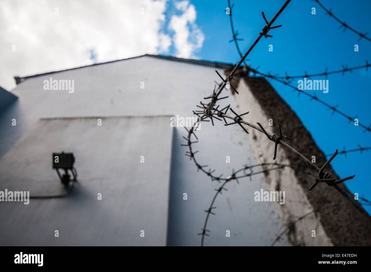 Barbed wire on the side of a building - Stock Image