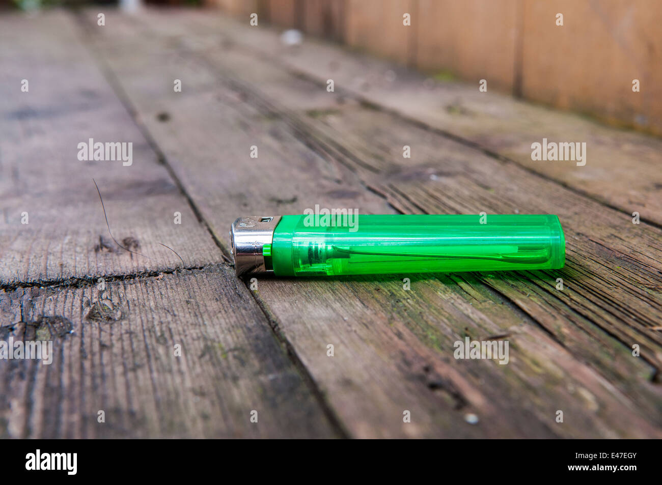 Cigarette lighter lying on a wooden table - Stock Image