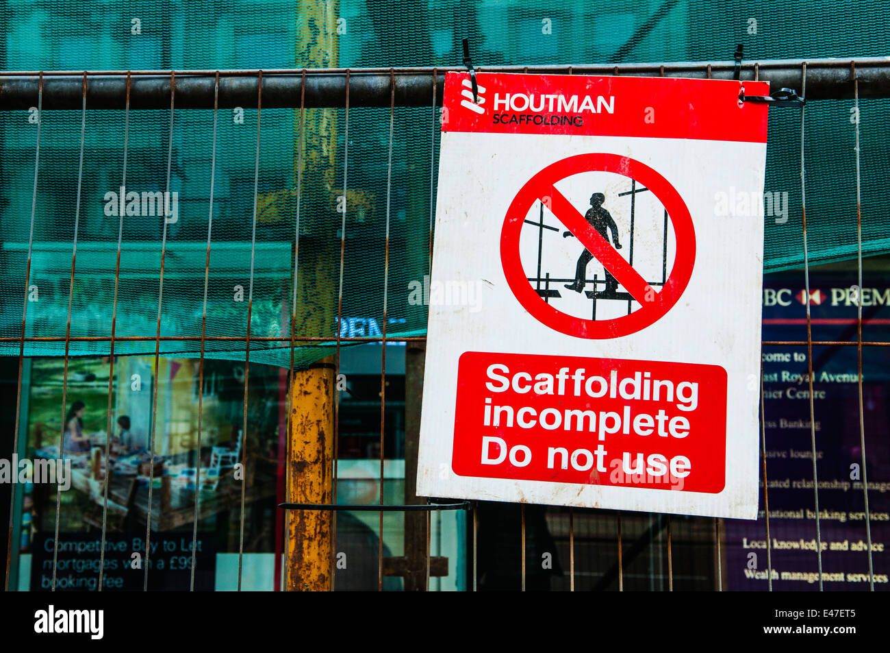 Warning sign at scaffolding warning that it is incomplete and do not use. - Stock Image
