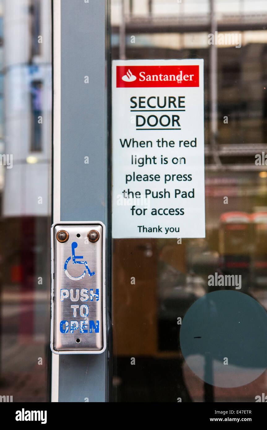 Button on a Santander Bank door advising customers to push the button for access. - Stock Image