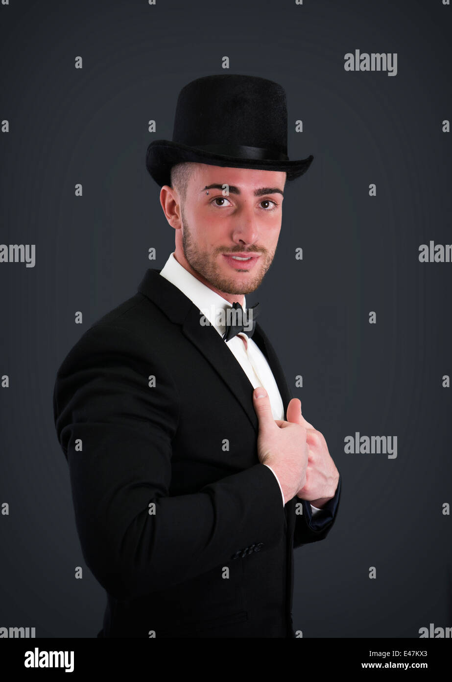 Attractive young businessman with suit, top-hat and bowtie on dark background - Stock Image