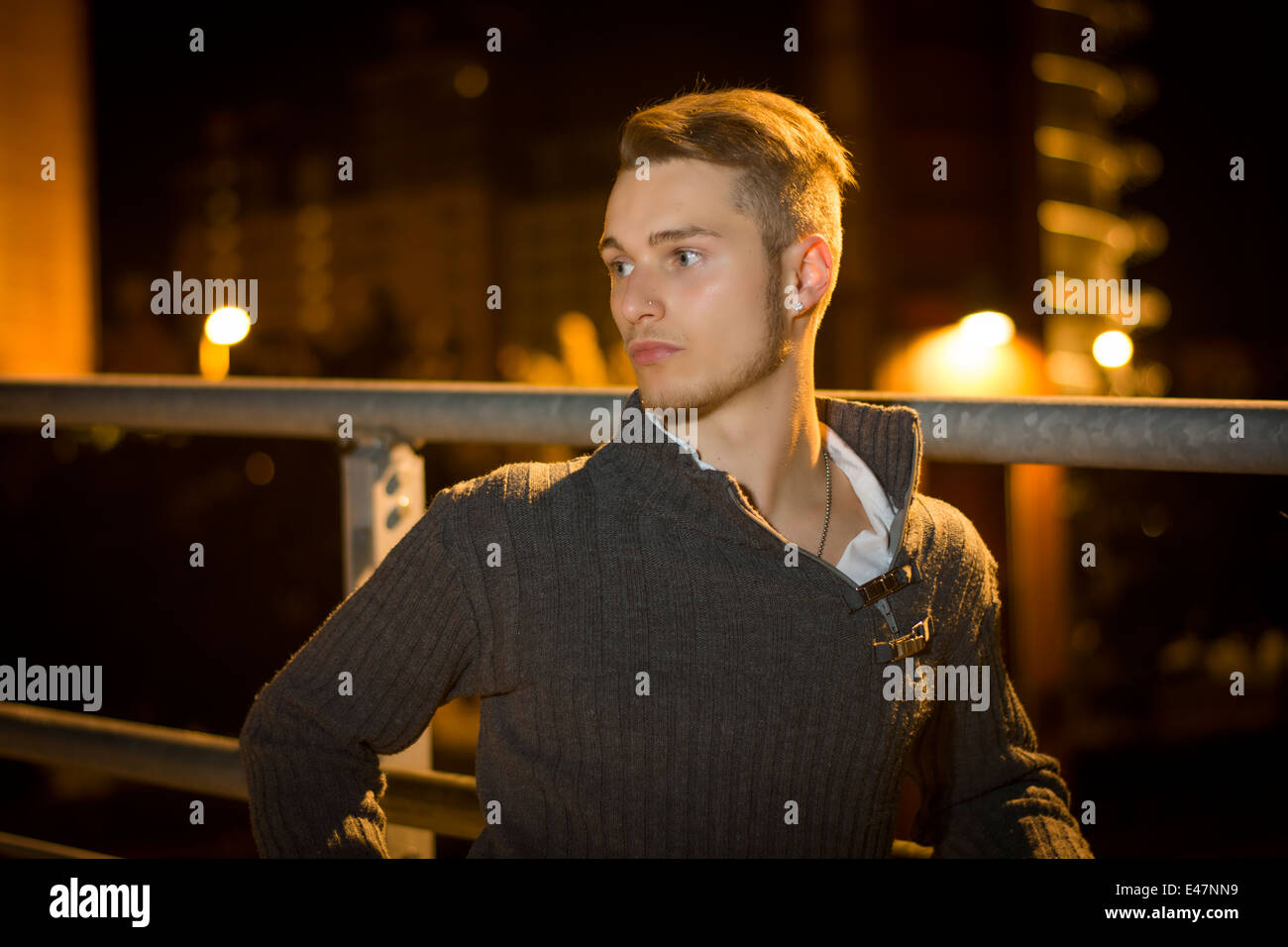 Handsome blond young man alone in urban setting, looking away, night shot - Stock Image