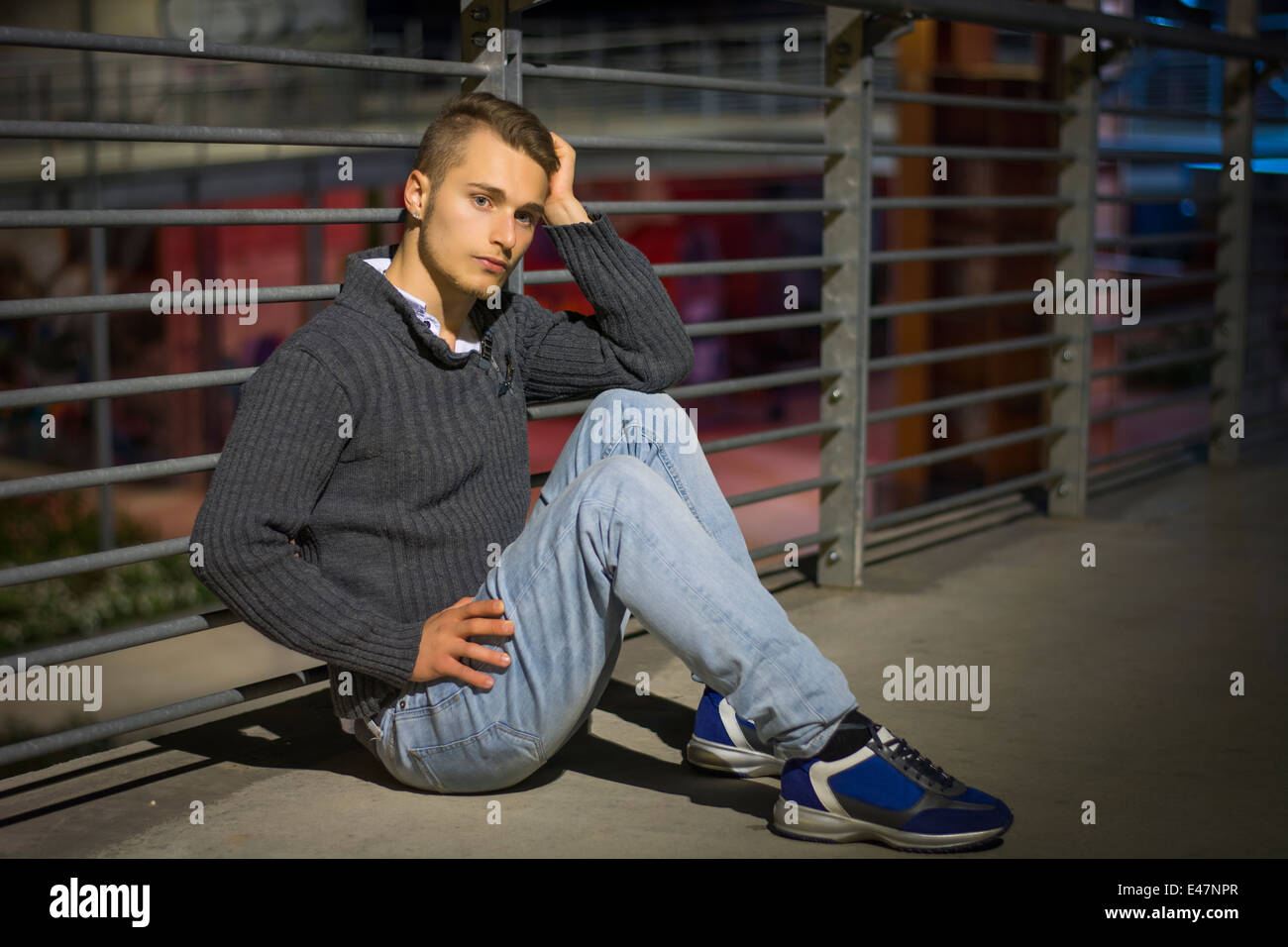 Handsome blond young man sitting alone in urban setting, looking at camera, night shot - Stock Image