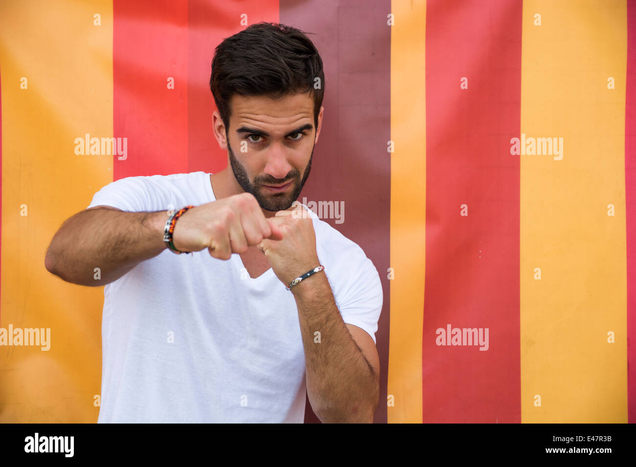 Angry handsome young man throwing punch to camera on colorful background - Stock Image