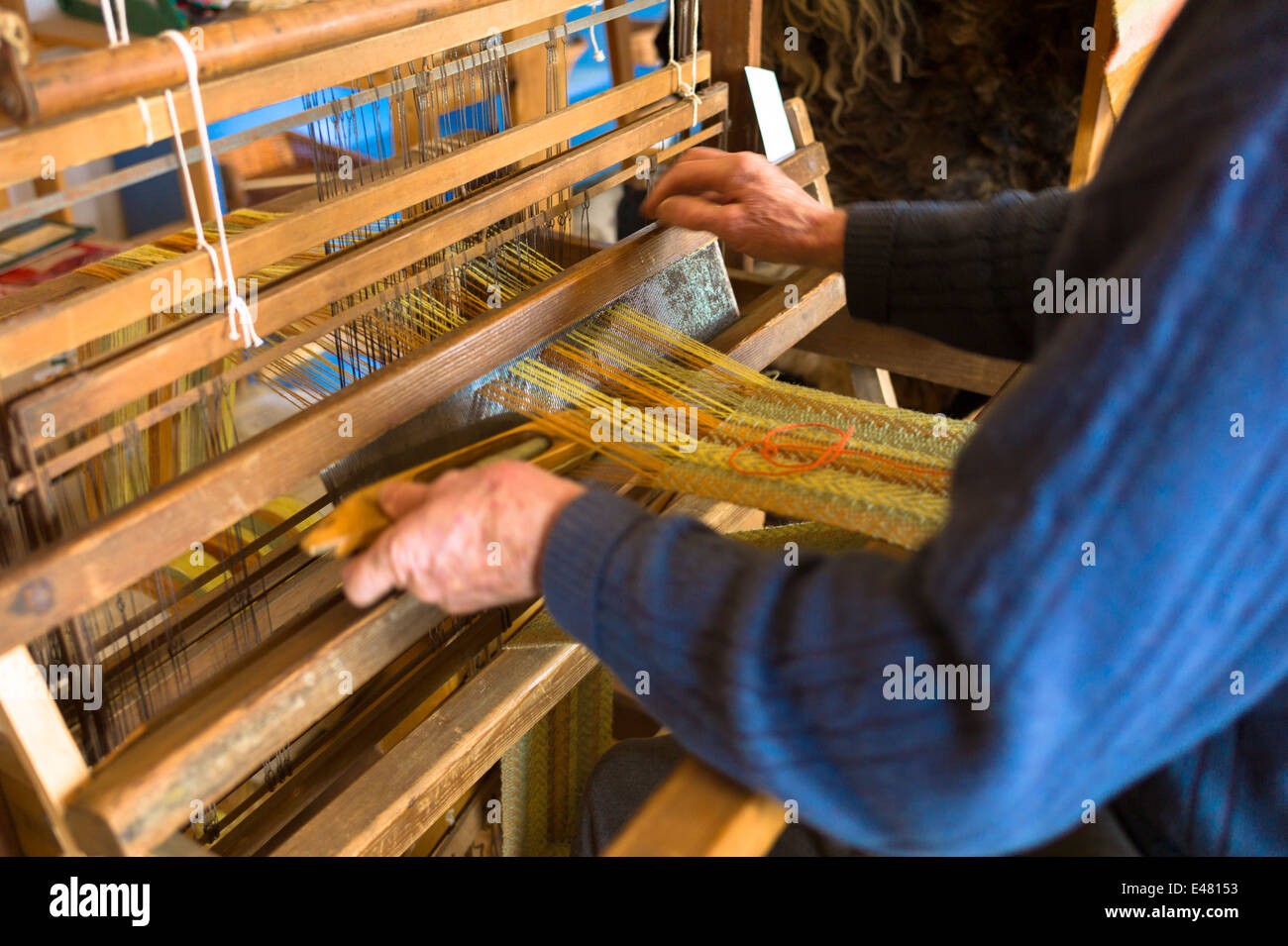 Craftsman using traditional loom to weave wool for handmade woollen scarf at Croft Wools Weavers in the Highlands - Stock Image