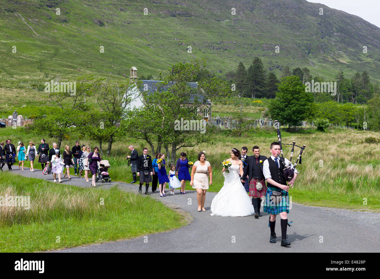 Highland Scottish wedding.  Piper leads procession of bride, groom and guests from Clachan Church in the Highlands Stock Photo