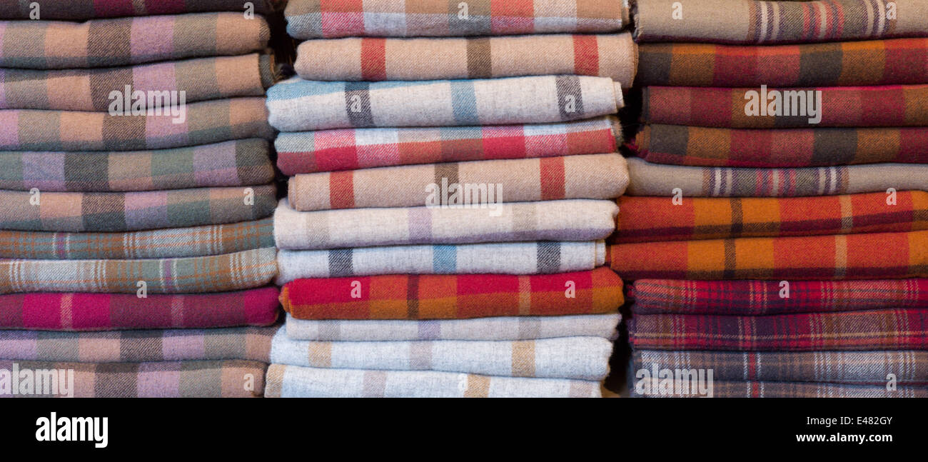 Checks, plaid and highland tartan lambswool throws and scarves for sale at Lochcarron Weavers in the Highlands of - Stock Image