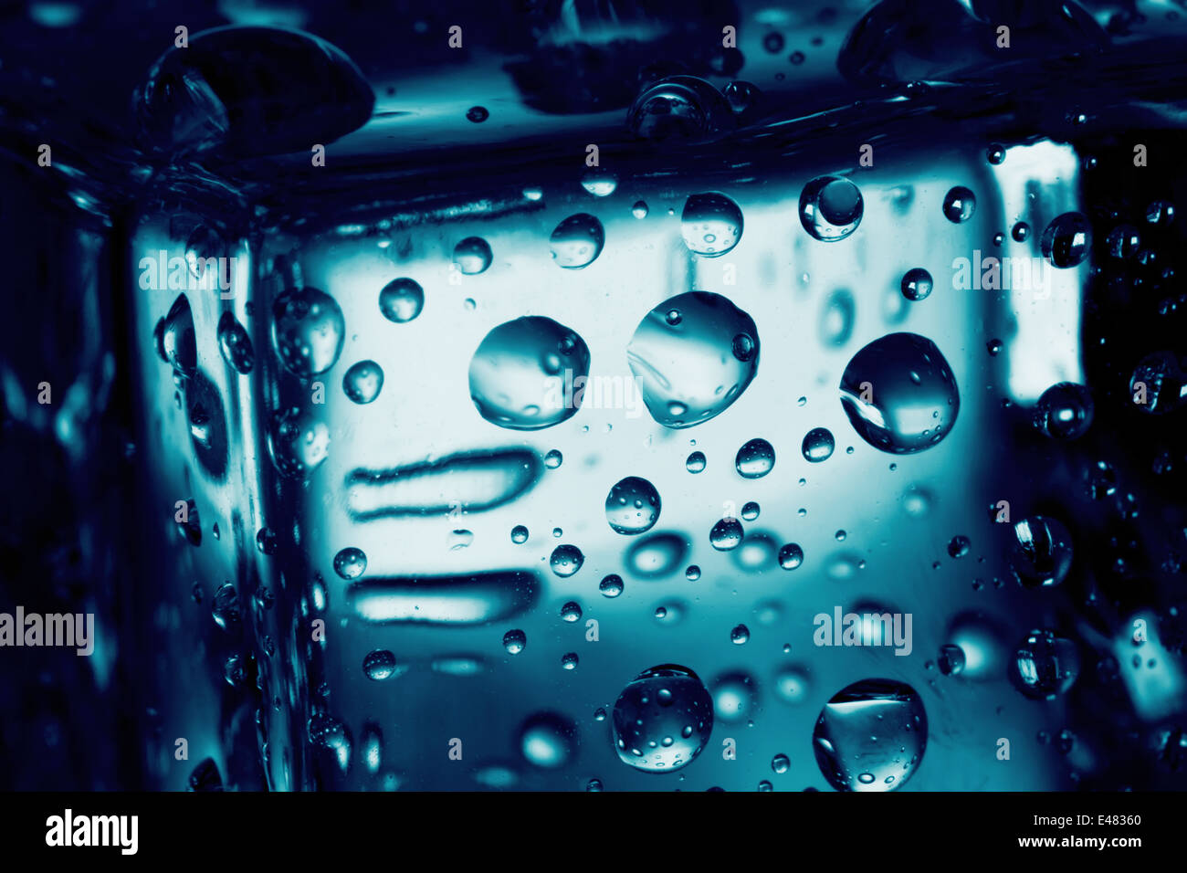 Background of ice cube with drops tinted blue - Stock Image