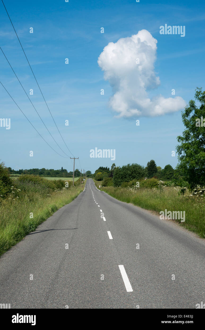 A straight country road in the UK, empty, leading to a vanishing point with blue sky and one white cloud - Stock Image