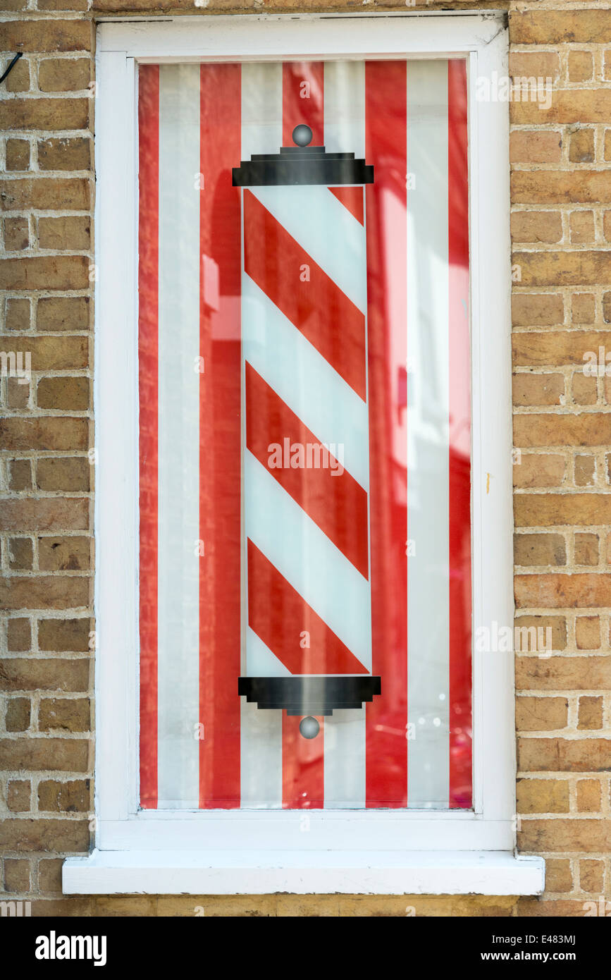 A red and white striped barbers pole outside a shop in Manchester UK - Stock Image