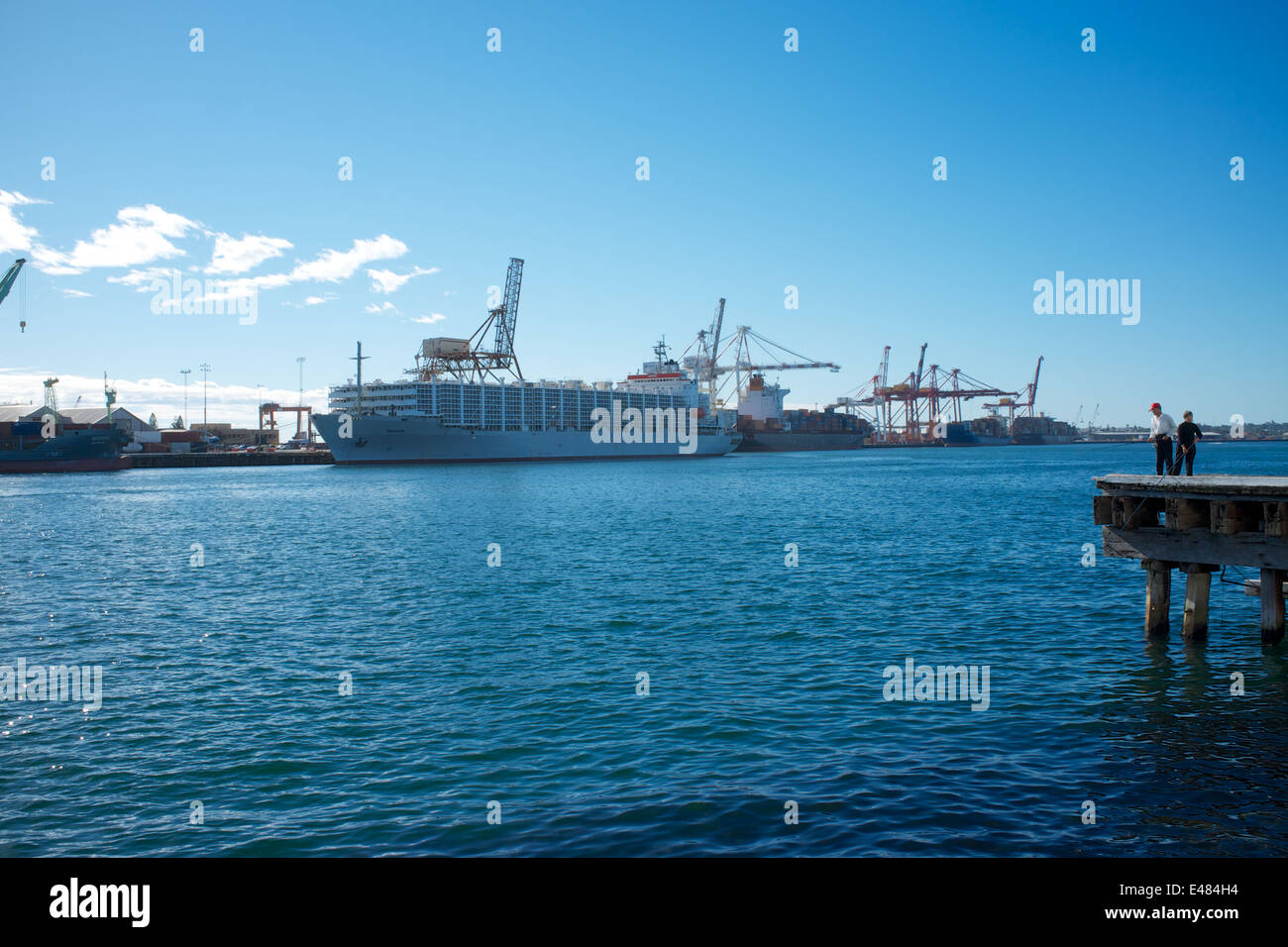 The port of Fremantle. There are two people fishing on the pier to the right of the picture.  The ship is the Maysora. - Stock Image