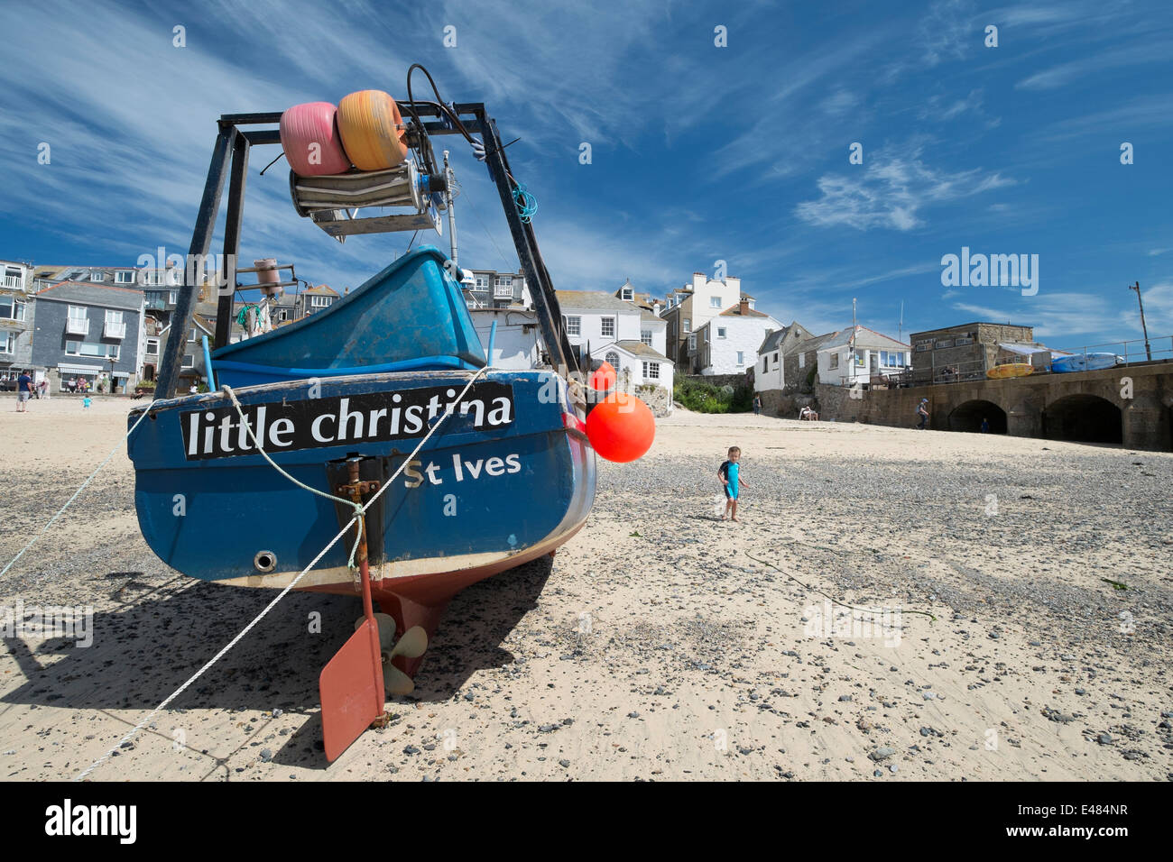 A young child walking on the beach at St Ives in Cornwall next to the fishing boat little christina Stock Photo