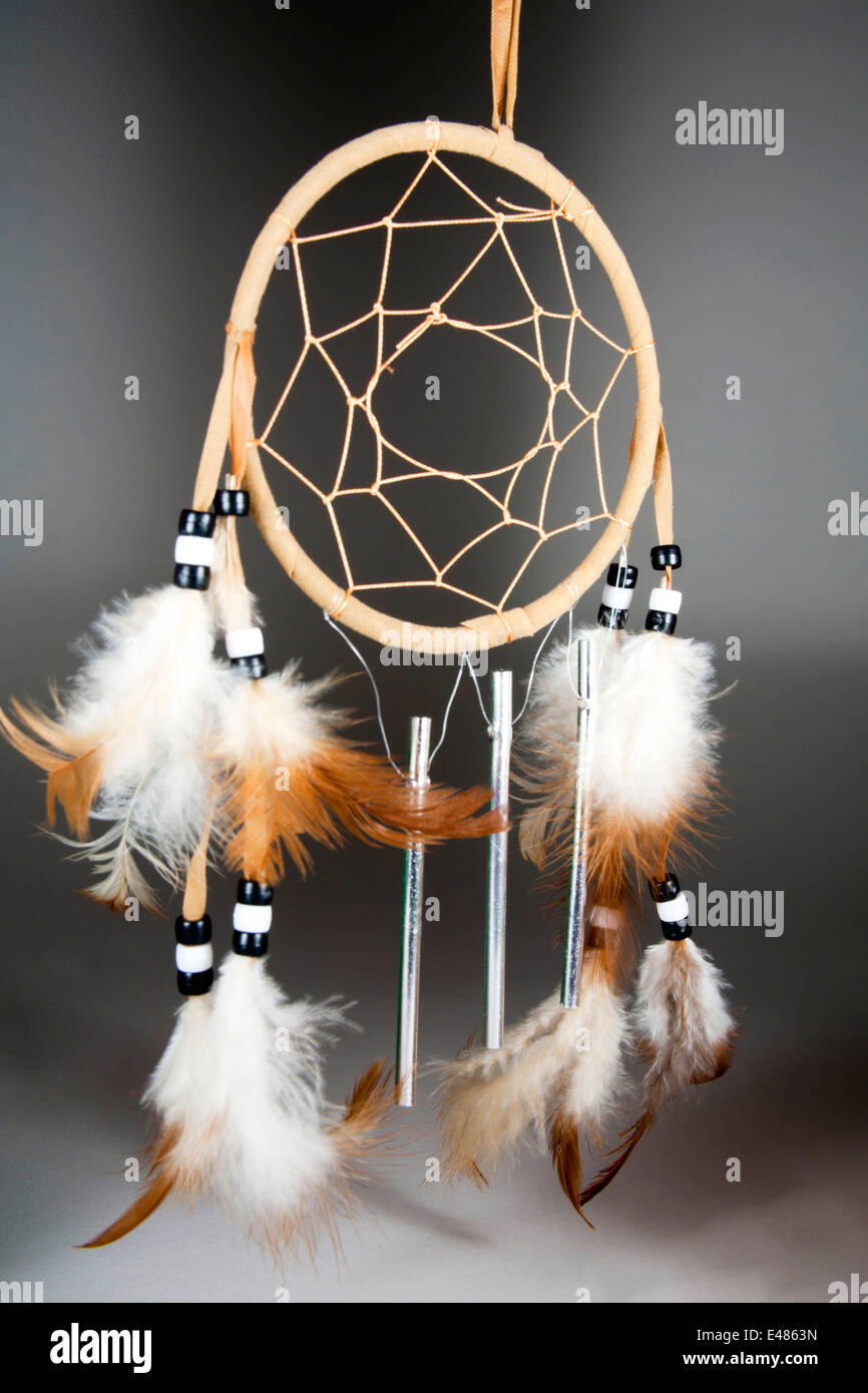 Native American Dream Catcher made from willow reeds with loose netting and decorated with feathers, beads and wind - Stock Image