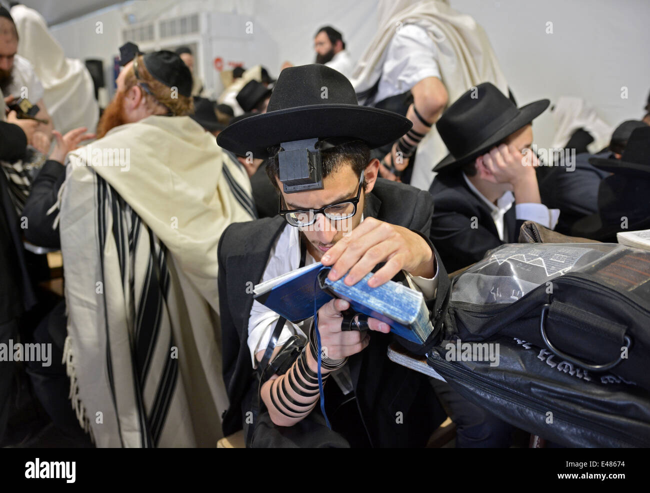 A religious Jewish young man reading at morning prayers at the Ohel in Cambria Heights, Queens. - Stock Image