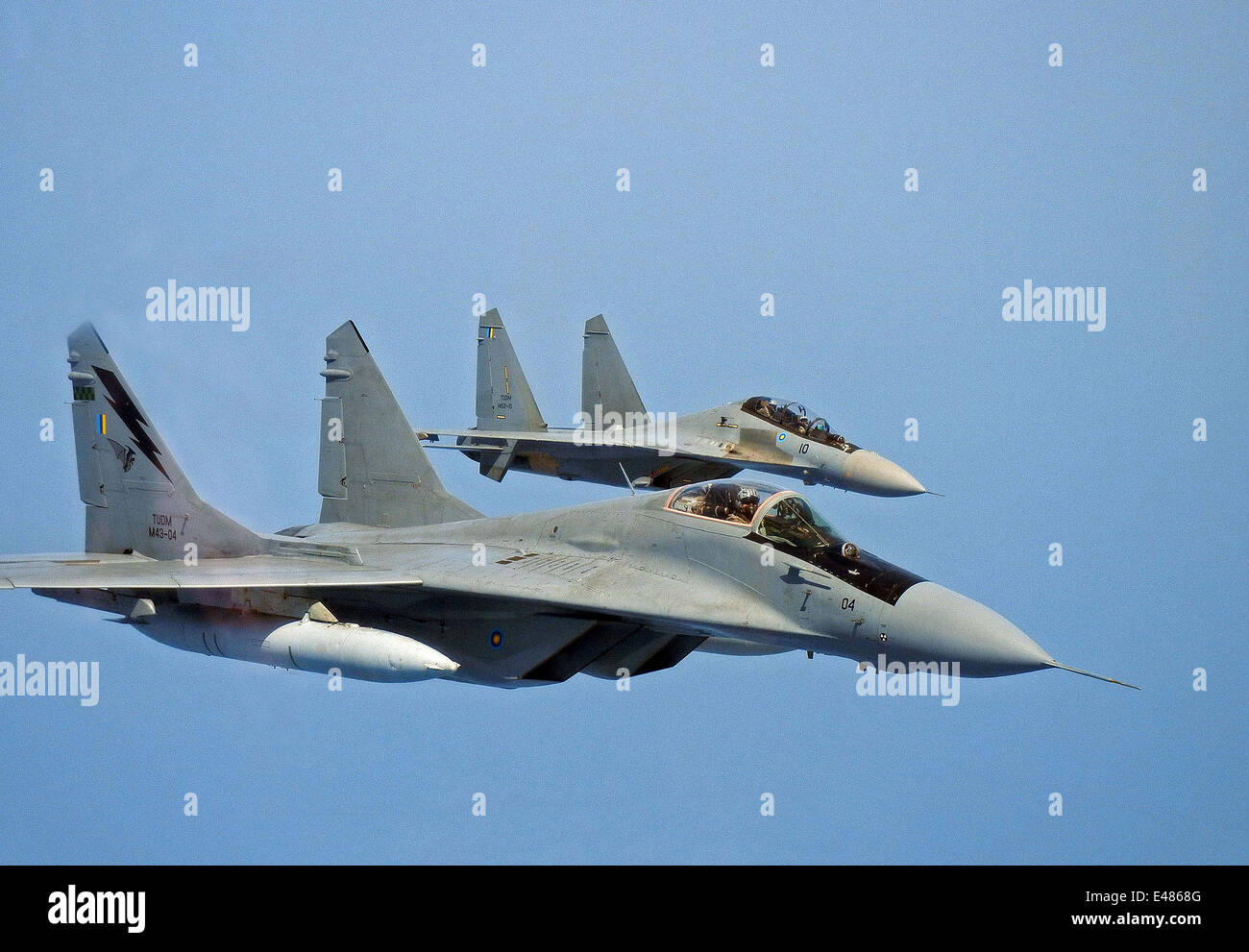 A Royal Malaysian Air Force MiG-29N Interceptor and Su-30MKM multirole fighter fly in wingtip formation during a - Stock Image