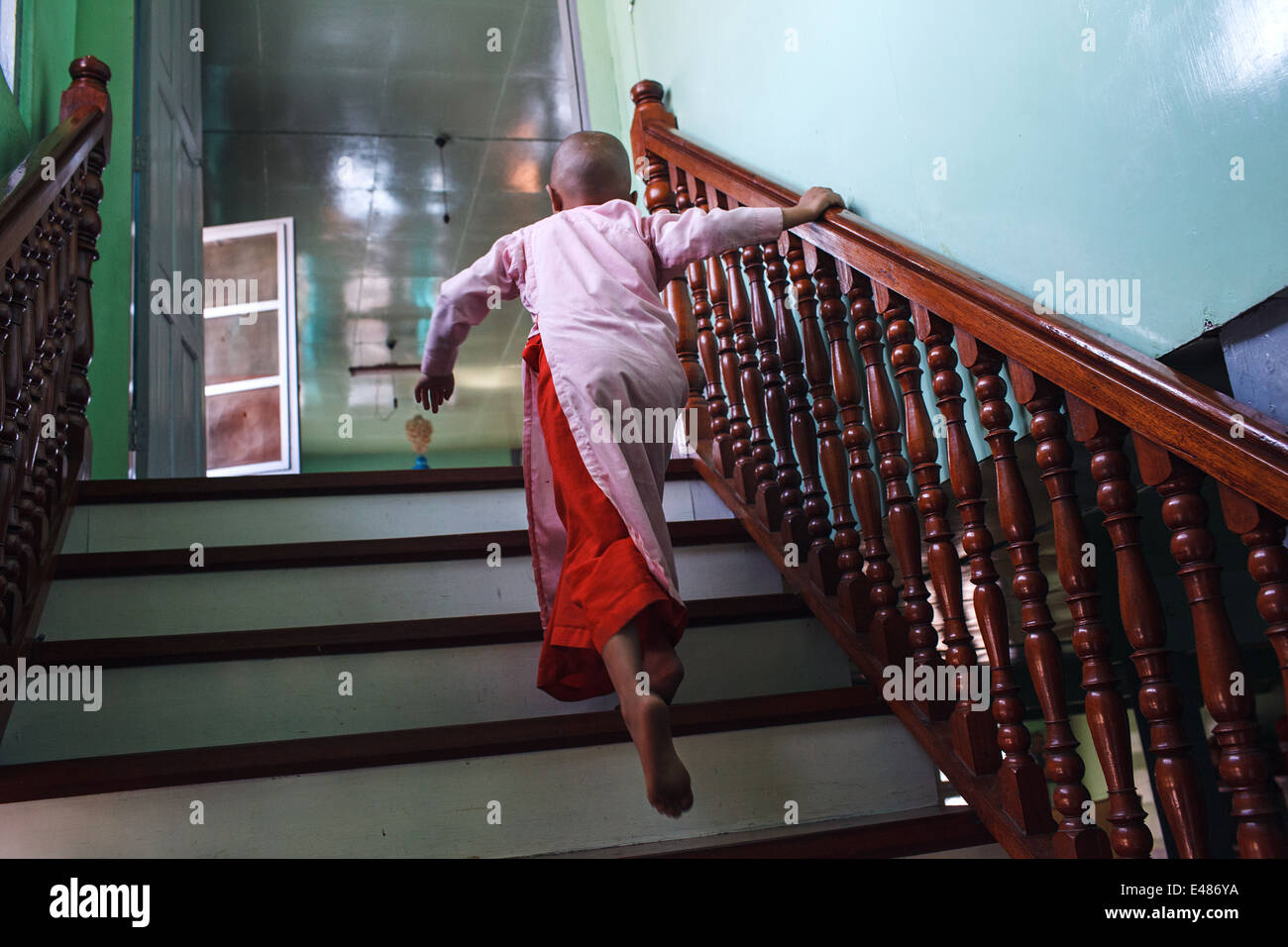 A young Buddhist novice nun runs up the stairs in a nunnery in Nyaungshwe, Myanmar (Burma) Stock Photo