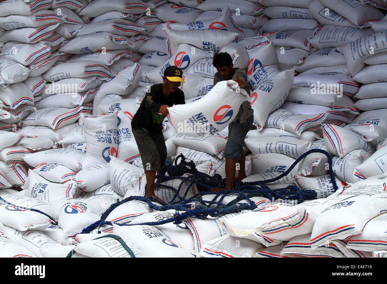 (140705) -- MANILA, July 5, 2014 (Xinhua) -- Workers unload sacks of imported rice at a port in Manila, the Philippines, - Stock Image