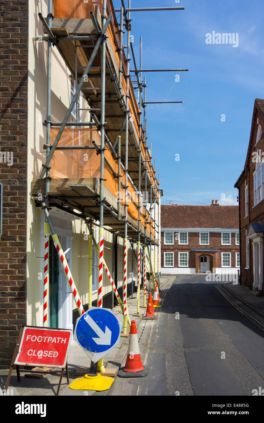 scaffolding erected on a two story building fitted with safety tapes netting cones and footpath closed signs in - Stock Image