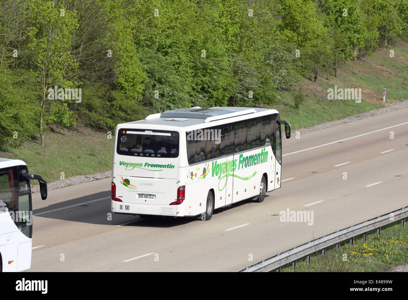 A Voyages Fromentin coach and part of another coach traveling along the m20 motorway in Kent, England - Stock Image