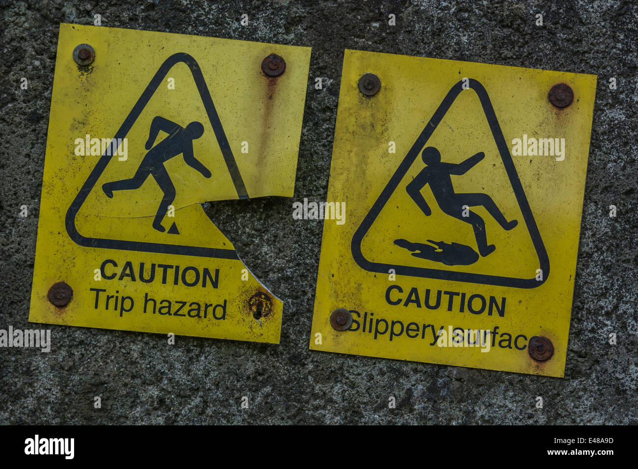 Close detail of two accident warning signs for 'trip' and 'slipping'. - Stock Image