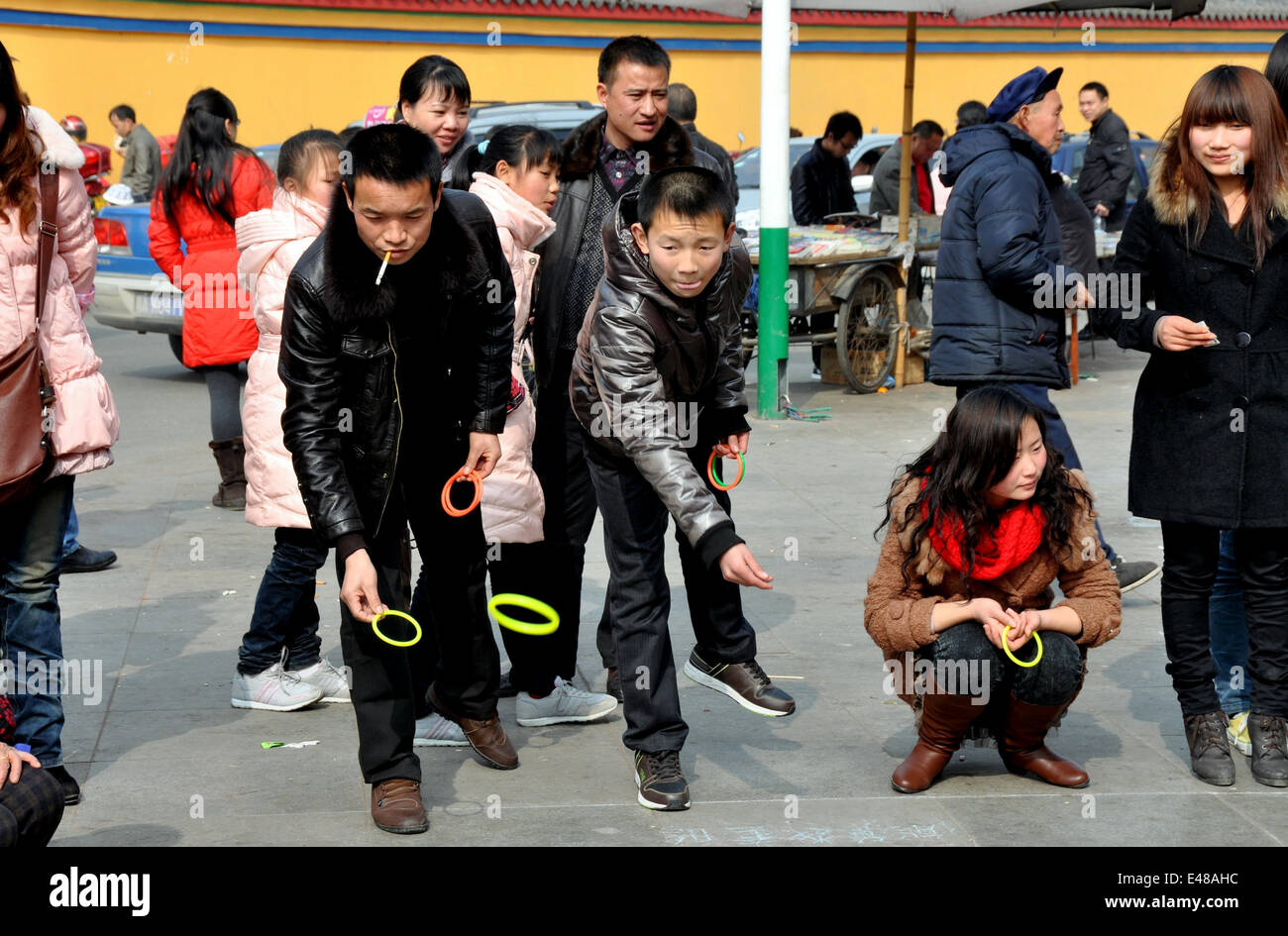 PENGZHOU, CHINA: People playing a game of ring toss hoping to loop a prize in Long Xing Square during the Chinese - Stock Image