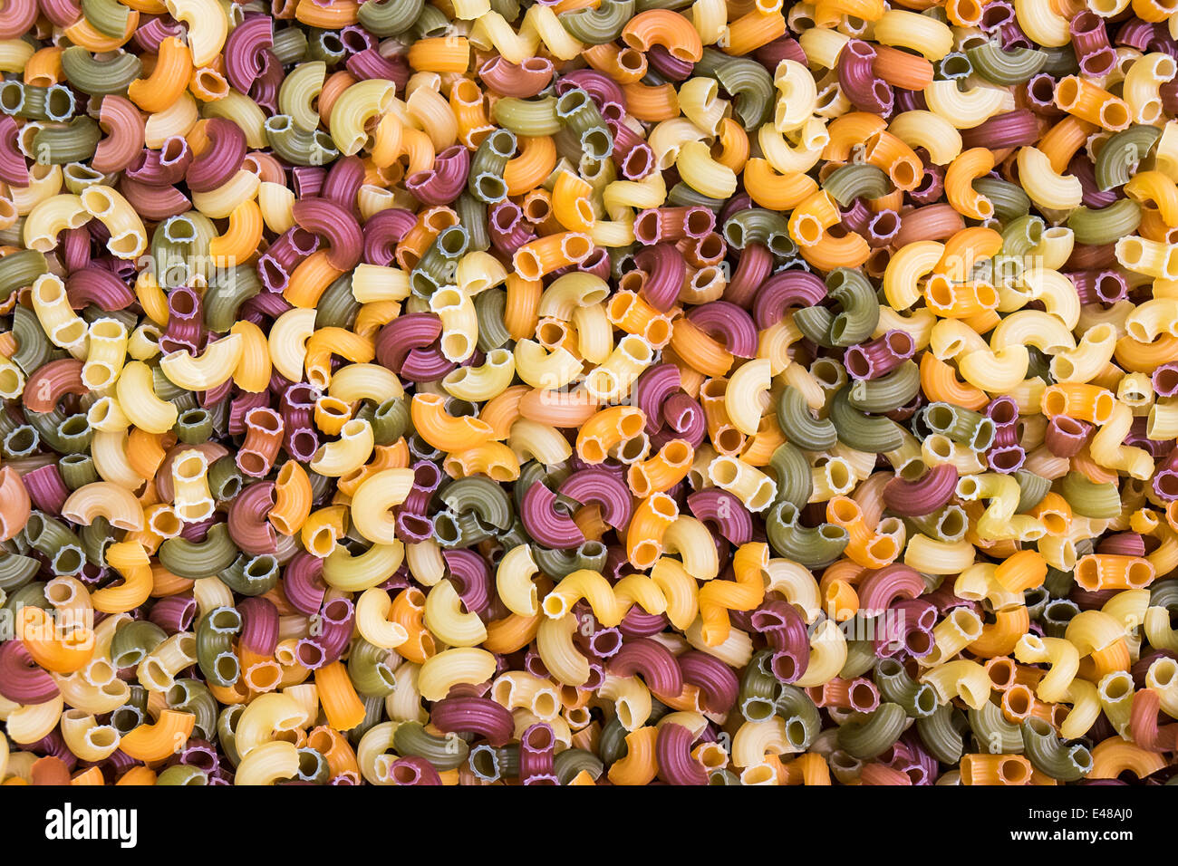 Background from multi-colored pasta, closeup filling the frame. - Stock Image
