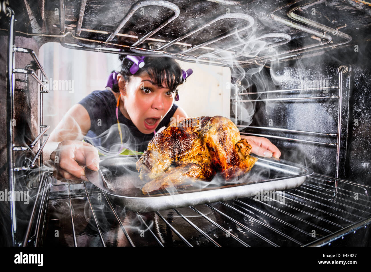 Housewife prepares roast chicken in the oven, view from the inside of the oven. Cooking in the oven. - Stock Image