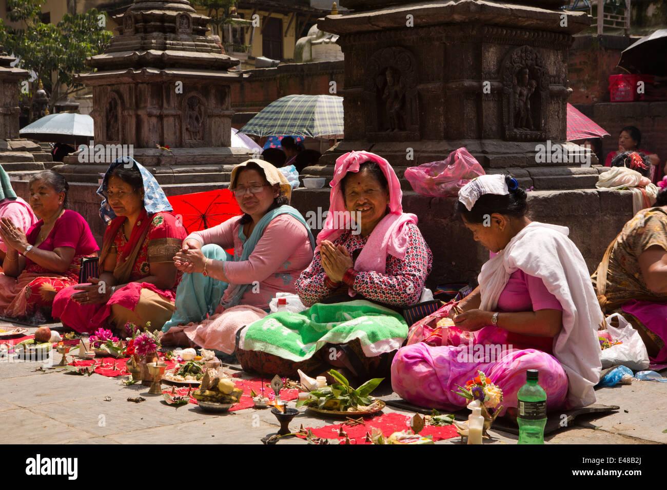 Nepal, Kathmandu, Kathesimbhu Stupa,Tibetan women undertaking ritual Buddhist puja - Stock Image