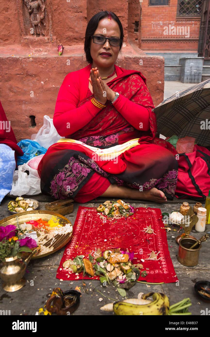 Nepal, Kathmandu, Kathesimbhu Stupa,Tibetan woman in red clothes undertaking ritual Buddhist puja - Stock Image